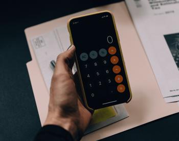 Mulher com a calculadora de aluguel no celular